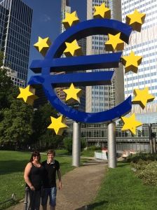 Mum and a finally-happy-looking Adam in front of the Euro sign.